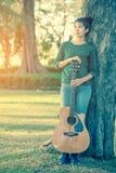 Muchacha asiática joven en el bosque que toca la guitarra Imagen de archivo libre de regalías