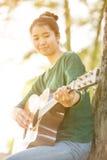 Muchacha asiática joven en el bosque que toca la guitarra Fotos de archivo libres de regalías