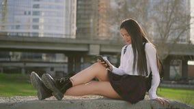 Muchacha asi?tica joven en uniforme escolar usando el tel?fono m?vil Hermoso adolescente y sonrisa almacen de video