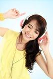 Muchacha asiática joven feliz con los auriculares Imágenes de archivo libres de regalías