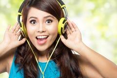 Muchacha asiática joven feliz con los auriculares Foto de archivo