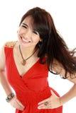 Muchacha asiática joven feliz en la acción que lleva el vestido rojo Imagenes de archivo