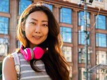 Muchacha asiática joven hermosa con la tableta Día de verano soleado en la situación de la ciudad con el auricular foto de archivo