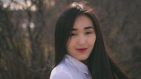 Muchacha asiática joven hermosa que da vuelta a la cámara El viento infla suavemente su pelo almacen de metraje de vídeo