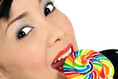 Muchacha asiática joven que come el lollipop Imágenes de archivo libres de regalías