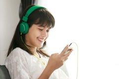 Muchacha asiática joven que escucha la música con el auricular y el smarthpho Fotografía de archivo