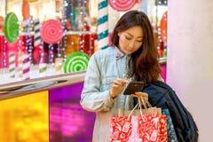 Muchacha asiática joven que hace compras en una alameda fotografía de archivo