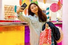 Muchacha asiática joven que hace compras en una alameda foto de archivo