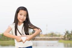 Muchacha asiática joven que hace el corazón con las manos Imágenes de archivo libres de regalías