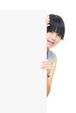 Muchacha asiática joven que se coloca detrás de una tarjeta en blanco Fotos de archivo