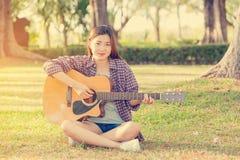 Muchacha asiática joven que toca la guitarra Imagen de archivo