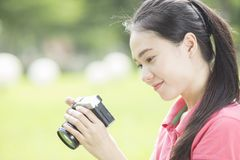 Muchacha asiática joven que toma la foto al aire libre con la cámara digital Foto de archivo