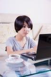 Muchacha asiática joven que usa el ordenador portátil Fotos de archivo libres de regalías