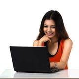Muchacha asiática joven que usa el ordenador portátil Fotografía de archivo