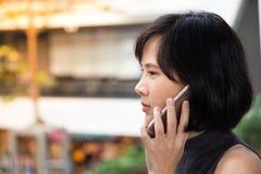 Muchacha asiática joven que usa el teléfono elegante en la alameda fotos de archivo