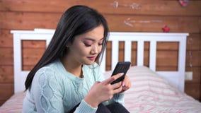 Muchacha asiática joven sonriente del primer medio que charla usando el smartphone que se sienta en cama en dormitorio almacen de metraje de vídeo