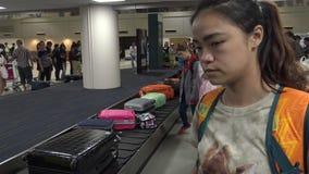 muchacha asiática 4k que espera el equipaje en el aeropuerto internacional de Don Mueang metrajes