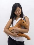 Muchacha asiática linda con un caballo del peluche Imagen de archivo