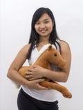 Muchacha asiática linda con un caballo del peluche Foto de archivo