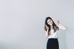 Muchacha asiática linda de la universidad que hace la actitud divertida del conejo, espacio de la copia en fondo gris de la pared Imágenes de archivo libres de regalías