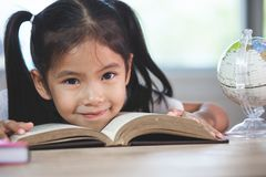Muchacha asiática linda del niño con un libro que sonríe en la sala de clase fotografía de archivo libre de regalías
