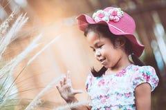 Muchacha asiática linda del pequeño niño que juega con la flor de la hierba Imagen de archivo