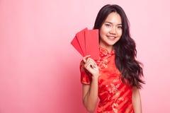Muchacha asiática linda en vestido rojo chino del cheongsam con el sobre rojo Fotografía de archivo libre de regalías