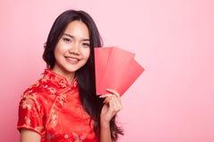 Muchacha asiática linda en vestido rojo chino del cheongsam con el sobre rojo Fotos de archivo