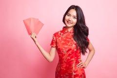 Muchacha asiática linda en vestido rojo chino del cheongsam con el sobre rojo Foto de archivo libre de regalías