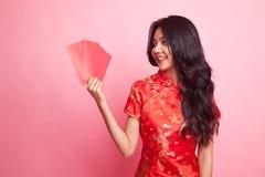 Muchacha asiática linda en vestido rojo chino del cheongsam con el sobre rojo Imagen de archivo