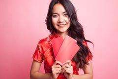 Muchacha asiática linda en vestido rojo chino del cheongsam con el sobre rojo Imágenes de archivo libres de regalías