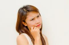 Muchacha asiática linda joven que piensa algo serio Imagen de archivo