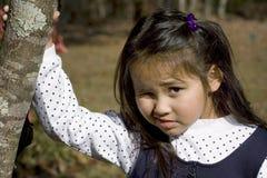 Muchacha asiática linda que bizquea del sol Imagenes de archivo