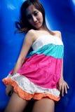 Muchacha asiática linda que mira el espectador que miente en una diapositiva azul Imagenes de archivo