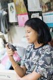 Muchacha asiática linda que mira el teléfono móvil Fotografía de archivo