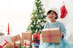 Muchacha asiática linda que sostiene una caja de regalo de la Navidad Fotografía de archivo libre de regalías
