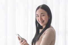 Muchacha asiática linda que usa el teléfono móvil por las ventanas de la mañana Foto de archivo