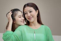 Muchacha asiática que abraza y que besa a su madre, día de la madre Imagenes de archivo