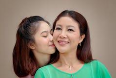 Muchacha asiática que abraza y que besa a su madre, día de la madre Imágenes de archivo libres de regalías