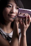 Muchacha asiática que aplica maquillaje Imágenes de archivo libres de regalías