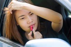 Muchacha asiática que aplica maquillaje mientras que en el coche Fotos de archivo