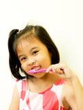 Muchacha asiática que aplica sus dientes con brocha foto de archivo libre de regalías