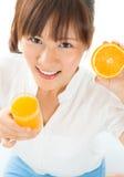 Muchacha asiática que bebe el zumo de naranja Fotografía de archivo libre de regalías