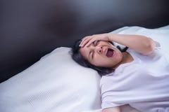 Muchacha asiática que bosteza en su cama y soñoliento cansado, síntomas y somnolencia imagen de archivo libre de regalías