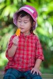 Muchacha asiática que come el helado en el verano en la parte posterior borrosa de la naturaleza Foto de archivo libre de regalías