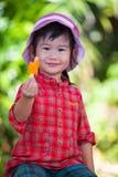 Muchacha asiática que come el helado en el verano en la parte posterior borrosa de la naturaleza Foto de archivo