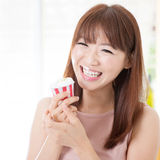 Muchacha asiática que come la magdalena imagenes de archivo