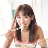 Muchacha asiática que come las bolas de masa hervida imagen de archivo
