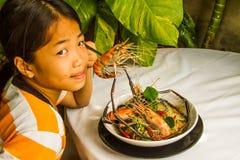 Muchacha asiática que come su comida. imagenes de archivo