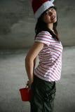 Muchacha asiática que desgasta el sombrero de santa que sostiene un cubo Fotos de archivo libres de regalías